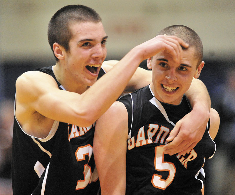 Gardiner High School teammates Aaron Toman, 33, left, and Jake Palmer, 5, right, celebrate as Palmer walks to the foul line for two free throws with seconds left on the semifinals of the Eastern Class B game against Medomak Valley High School at the Bangor Auditorium Wednesday. Gardiner defeated Medomak Valley 57-46.