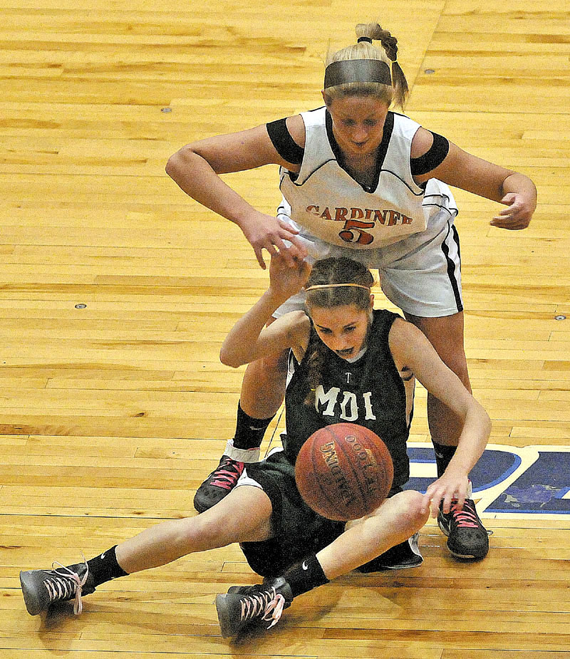 Gardiner High School's Paige Pilsbury, 5, top, fights for the loose ball with Mount Desert Island High School's Sarah Phelps, 5, bottom, in the first half of the Eastern Class B quarterfinals game at the Bangor Auditorium Saturday. Gardiner defeated MDI 63-38.