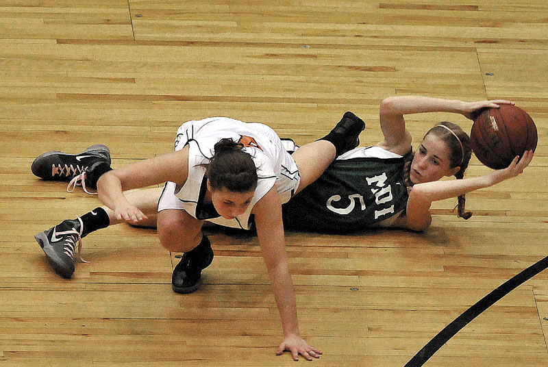 Photo by Michael G. Seamans Gardiner High School's Kylee Granholm, 4, top, tries to avoid Mount Desert Island High School's Sarah Phelps, 5, bottom, after Phelps lost control of the ball in the first half of the Eastern Class B quarterfinals game at the Bangor Auditorium Saturday. Gardiner defeated MDI 63-38.