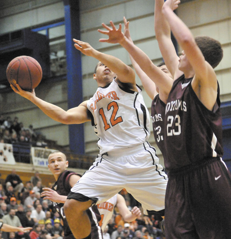 Gardiner High School's Alonzon Connor, 12, drives to the hoop against Nokomis High School defenders Chandler Foss, 32, center, and teammate Andrew Cartwright, 23, right, in the first half of the Eastern Class B quarterfinals game at the Bangor Auditorium Friday. Gardiner won 56-47 in over time.