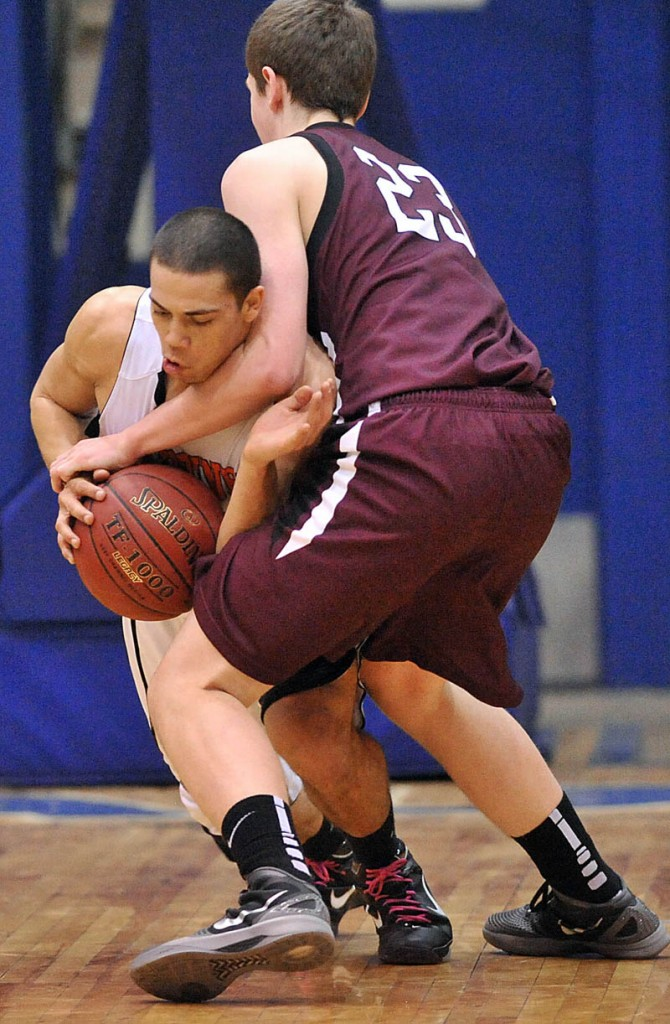 Gardiner High School's Alonzo Connor, 12, facing, and Nokomis High School's Andrew Cartwright, 23, fight for the ball in the first half of the Eastern Class B quarterfinals game at the Bangor Auditorium Friday. Gardiner won 56-47 in over time.