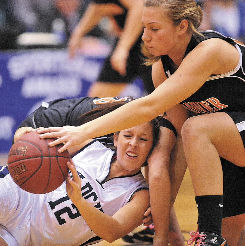 Gardiner High School's Kelly MaComber, 22, battles for the loose ball with Presque Isle High School's Chelsea Nickerson, 12, in the first half of the Eastern Class B semi-finals at the Bangor Auditorium Wednesday.