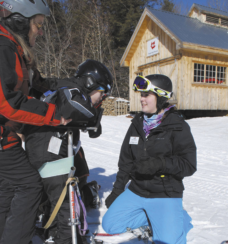 GIVING BACK: Margaret Adams of Gould Academy coaches Max Thorman of Crescent Park Elementary earlier this month at Sunday River as Robyn Kanter holds Thorman. Adams has helped Gould's long-time ski instructor program extend its reach into the Maine Adaptive community, where volunteers like Kanter help teach athletes with disabilities how to ski and ride.