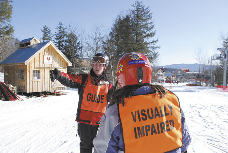 "LENDING A HAND: Gould Academy junior Liam Gillis helps instruct a visually impaired skier at Sunday River earlier this month. Gillis helped Gould Academy start up the portion of its ski instructor program that works with Maine Adaptive. Gould's ski instructor program, ""Rugrats,"" has been teaching local elementary students to ski for free for 25 years."