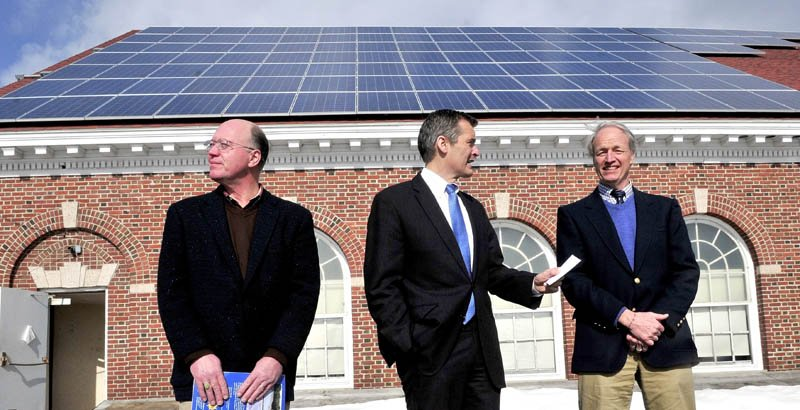 ENERGY FROM ABOVE: Glenn Cummings, center, president and CEO of Good Will-Hinckley/Maine Academy of Natural Sciences, on Monday is flanked by Steve Cole, left, of Coastal Enterprises and Bill Behrens of ReVision Energy under the 110 solar panels that produce energy for the Prescott Memorial Hall building on campus.