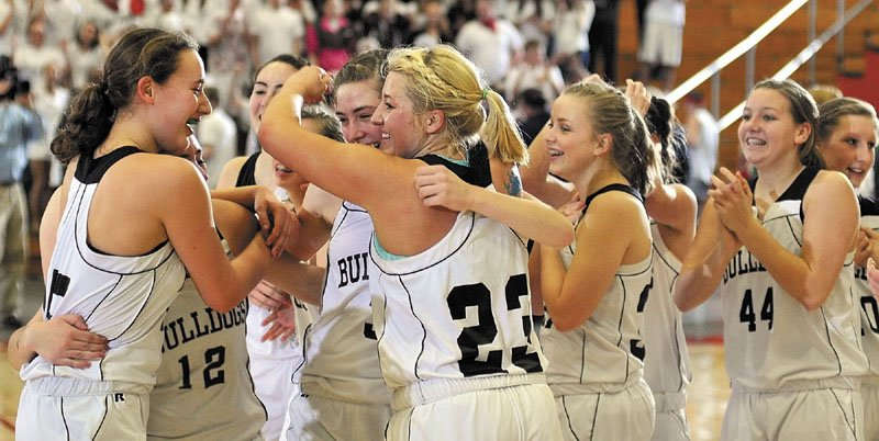 WE DID IT: The Hall-Dale girls basketball team celebrates at midcourt after winning the Western C championship game Saturday night at the Augusta Civic Center. The top-seeded Bulldogs beat No. 7-seeded Waynflete 43-36.