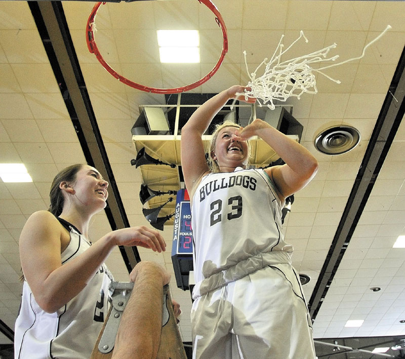 Staff photo by Joe Phelan Hall-Dale seniors Paley Sweet, left, and Carylanne Wolfington celebrate atop the ladder after cutting down the nets following the Bulldogs victory in the Class C West championship game on Saturday night at the Augusta Civic Center.