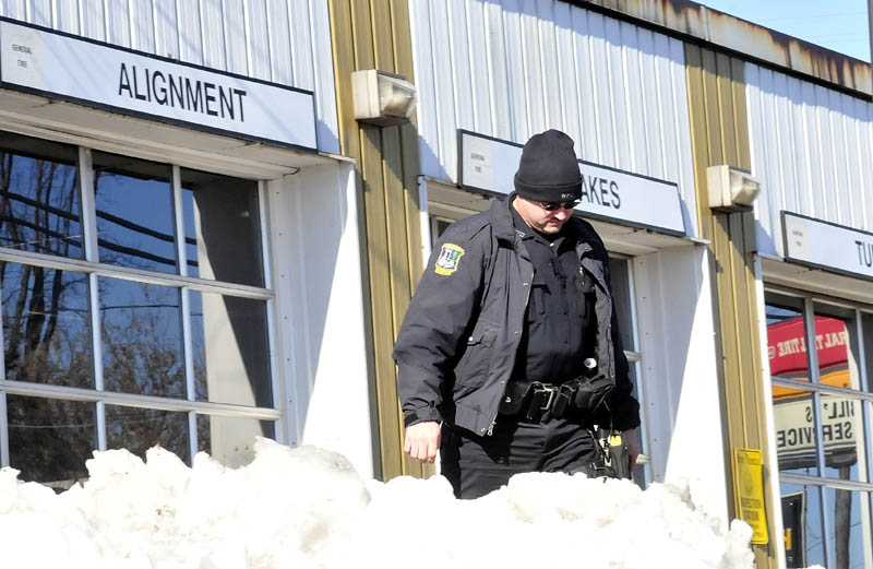 ASSAULT SEARCH: Waterville police officer Steve Brame searches the parking lot at Bill's Tire business in Waterville for evidence an assault took place involving Lance DiPietro and another man on Monday.
