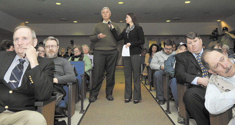 Adrienne Bennett, right, press secretary for Gov. LePage, holds the microphone for Bob Farley, of Norridgewock, as he asks the governor a question regarding religion in school during a town hall meeting at Madison Junior High School Thursday night.