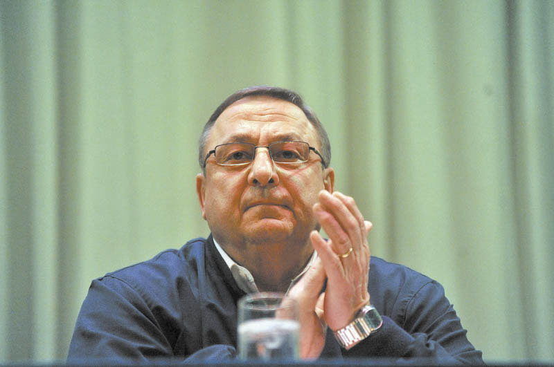 Gov. Paul LePage claps as members of the discussion panel are introduced during a town hall meeting at Madison Junior High School Thursday night.