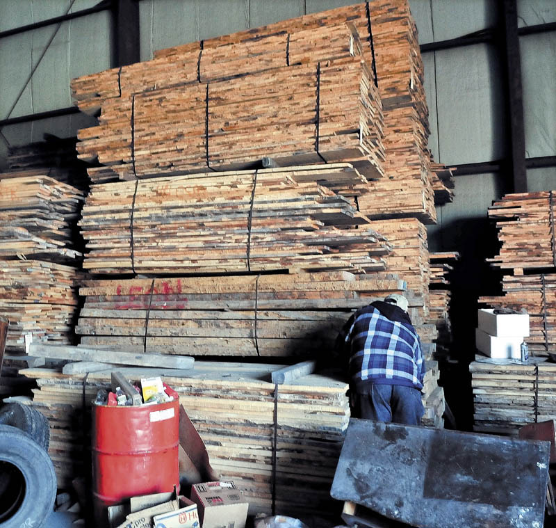 LUMBER TAKEN: An employee at Premium Log Yards Inc. in North Anson looks over stock of bundled curly maple boards stored in a building on Thursday.