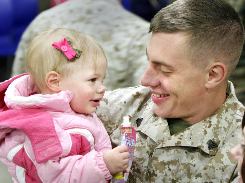 Cpl. Andrew Arseneault of Blue Hill is all smiles Wednesday as he holds his 17-month-old daughter, Arianna, after arriving in Brunswick with of Company A, 1st Battalion, 25th Marine Regiment, 4th Marine Division.