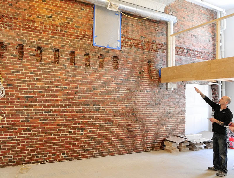 Patrick Guerette points at an old door above the notches in the brick wall during a tour of the apartments being built in the old Chernowsky's building in downtown Augusta. He said that the notches used to support beams for a former fourth floor.