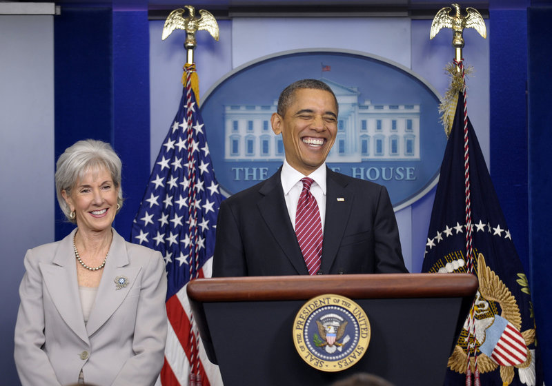 President Barack Obama, standing with Health and Human Services Secretary Kathleen Sebelius, smiles Friday before announcing the revamp of his contraception policy requiring religious institutions to fully pay for birth control. He delivered a statement in the Brady Press Briefing Room of the White House in Washington.