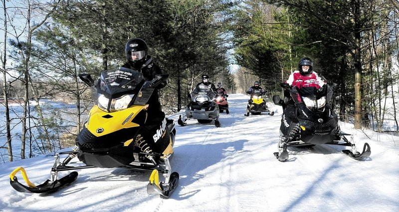 REVVED UP: Scott Newton, left, of North Country Rivers in Bingham, leads a group of snowmobilers down the Interconnected Trail System 87 trail recently. The snowmobile rental business is counting on improving snow conditions for the rest of February and March to make up for a poor start to the season because of low snowfall totals.