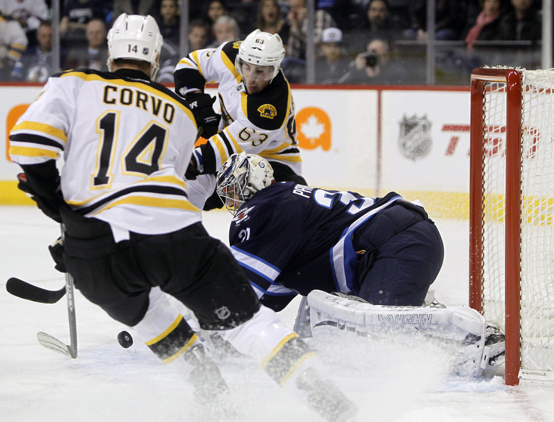 Ondrej Pavelec, goalie for Winnipeg, makes one of his 13 first-period saves as Boston's Joe Corvo, left, and Brad Marchand converge. Pavelec made 31 saves in a 4-2 Winnipeg win.