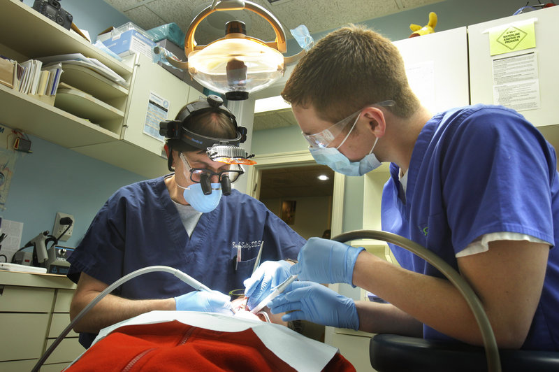 Dr. Barry Saltz, left, assisted by Tim Kilgo, works Monday with patient Danielle Romanoff in his Portland dentistry office. Saltz is pleased that UNE's new dental school in Portland, which opens in the fall of 2013, will send students on rotations around the state to provide care.