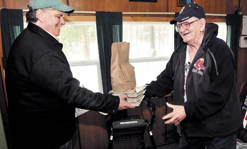 In this 2014 file photo, Clifford Groder Sr., right, of Skowhegan, accepts delivery of three days of food from Ryan Poirier, volunteer driver for Spectrum Generations' Meals on Wheels program.