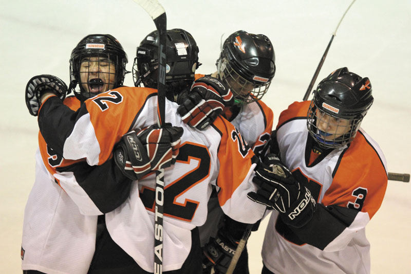 A REASON TO SMILE: After scoring a second period goal, Skowhegan Area High School's Trey Michonski (22) gets a hug from Anthony Paul, left, and several other teammates during Friday night's game against Gray New Gloucester Poland at Sukee Arena in Winslow.