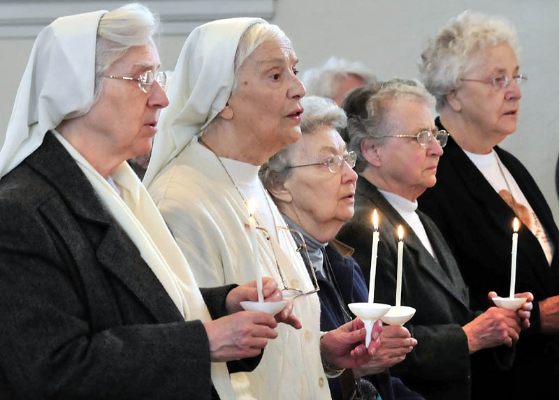 SOLEMN SERVICE: Sisters of the Blessed Sacrament convent lead a candlelit procession during a service on Thursday at St. Francis de Sales in Waterville. The Catholic church will hold a closing Mass on Sunday and will be demolished later this year to make way for an elderly housing complex.