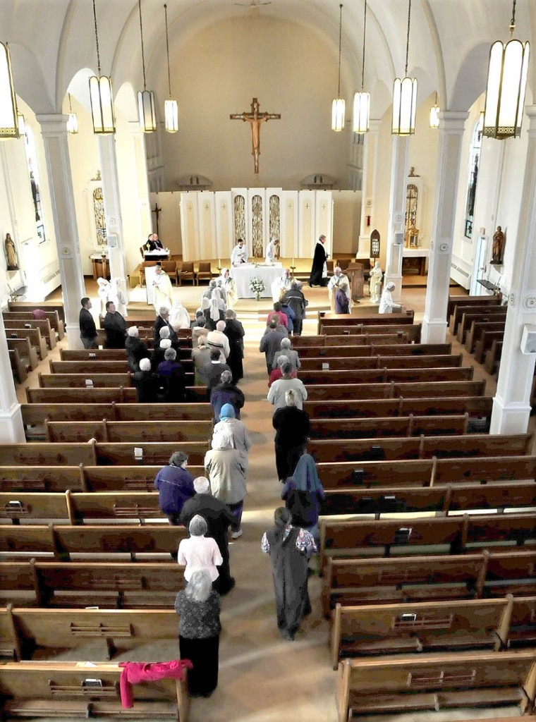 FINAL DAYS: The Rev. Joseph Daniels, left, and the Rev. Jacques Dolbec conduct communion services with parishioners at St. Francis de Sales Church in Waterville on Thursday.
