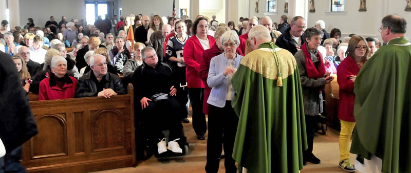 FINAL MASS: The Most Rev. Richard J. Malone, center, Bishop of Portland, conducts Communion services during the final Mass at St. Francis de Sales Church in Waterville. The church, which was filled to capacity on Sunday, will be demolished this year to make room for an elderly housing project.