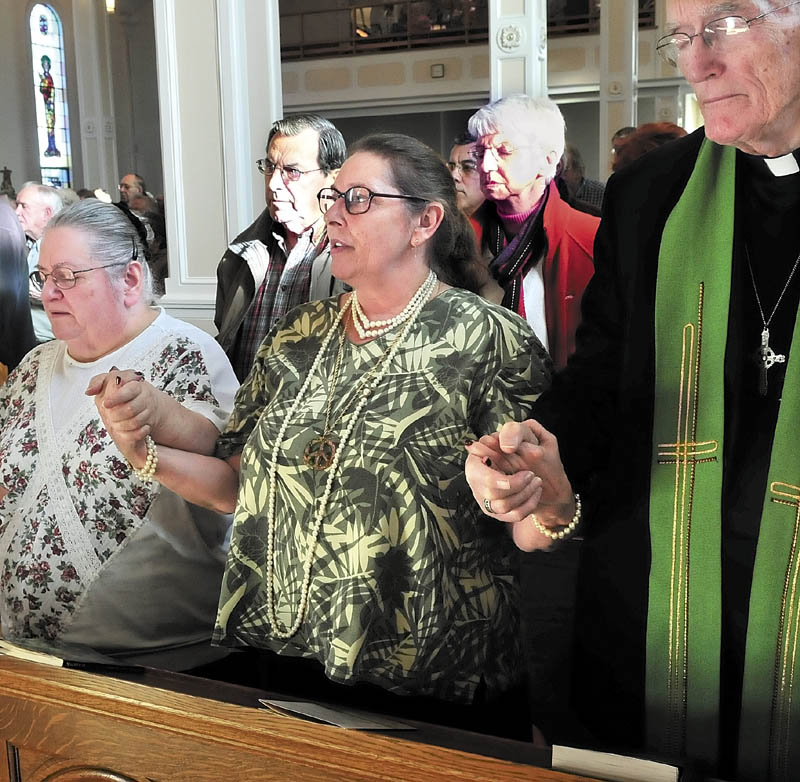 TOGETHER: Katheryn Moses, left, Linda Hook and Father Miles Brookes hold hands as they, and the congregation, recite the Lord's Prayer during the final mass at St. Francis de Sales Church in Waterville on Sunday.