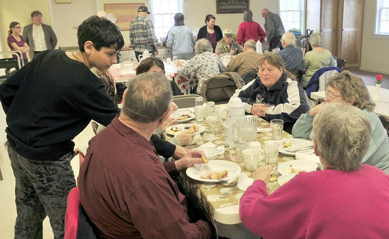 WARMTH: Volunteer Wyatt Howe of Somerset Valley Academy waits on patrons at the Norridgewock Warming Center during lunch at the First Congregational Church on Thursday. In a year the center has grown to 70 people having dinner on Thursdays. At left in back is The Rev. Nathan Richards.