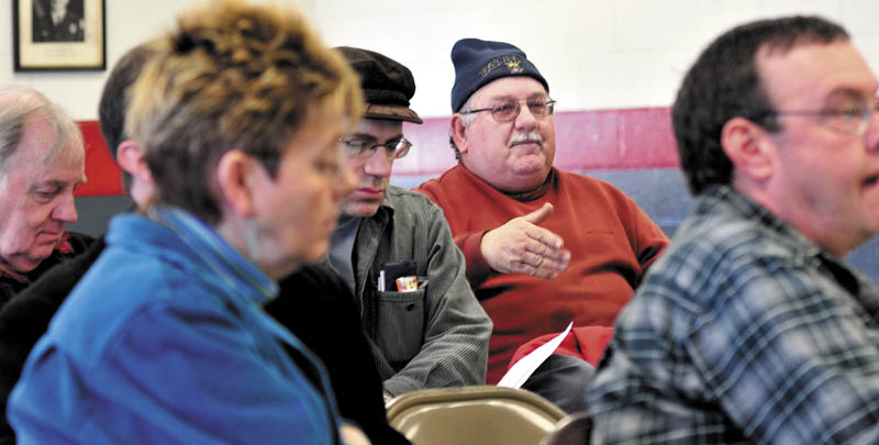 BY THE PEOPLE: Jerry Quirion, center, makes a point Sunday at Winslow's Democratic caucus at the Winslow Fire Department.
