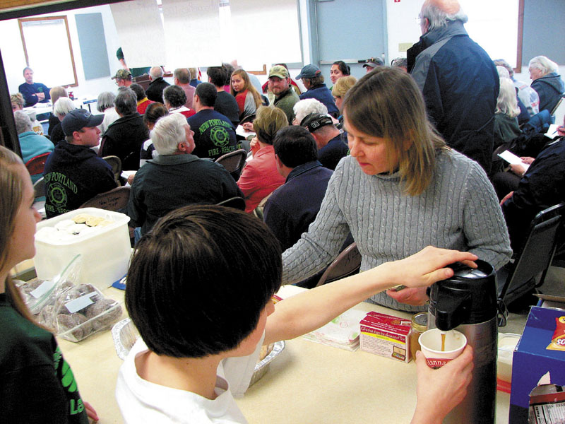 RAISING FUNDS: Taylor Bartlett, 13, left, and Tyler Reichert, 14, both of New Portland, serve resident Nora West during the New Portland Town Meeting on Saturday. The two were selling food in order to raise money for their eighth grade trip to Washington, D.C.