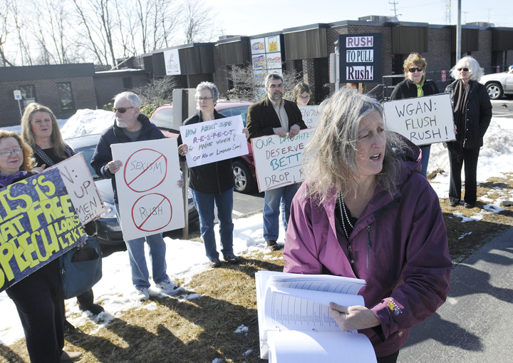 "Annie Finch of Falmouth holds a petition calling on radio station WGAN to stop airing ""The Rush Limbaugh Show."" Finch was joined by a group of supporters outside the Portland Radio Group offices today."