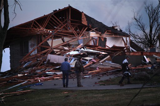 Doug Imhoff, center, stands in front of his home, in Piner, KY Friday. He had taken refuge in its basement as an apparent tornado swept through the area Friday evening. (AP Photo/The Enquirer, Carrie Cochran)