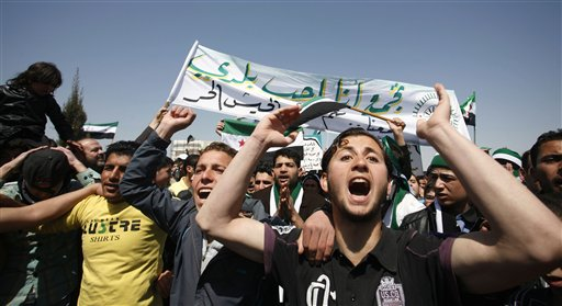"""Syrians anti-Bashar Assad slogans in front of the Syrian embassy during a protest in Amman, Jordan, today. The Arabic banner reads, """"I love my country and the Free Syrian Army."""" In his first public appearance since fleeing to Jordan two months ago, blind Syrian cleric Ahmad al-Sayasneh preached to 1,000 Syrian anti-Assad protesters today to """"remain steadfast until our tyrant leadership is ousted."""""""