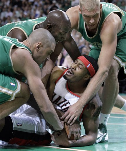 Portland Trail Blazers power forward Craig Smith tries to protect the ball as he is tied up by Boston Celtics forward Sasha Pavlovic, left, forward Kevin Garnett, middle, and center Greg Stiemsma, right, on Friday in Boston.