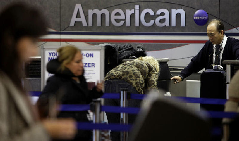 Travelers check in at an American Airlines counter at LaGuardia Airport in New York. Air fares will remain high for at least a decade, the FAA predicts, because with little existing competition, airlines have no incentive to lower prices. (AP Photo)
