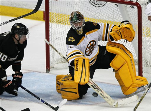 Boston Bruins goalie Marty Turco, right, stops the puck as Anaheim Ducks right wing Corey Perry looks on in the third period of an NHL hockey game in Anaheim, Calif., on Sunday, March 25, 2012. The Bruins won 3-2. (AP Photo/Christine Cotter)