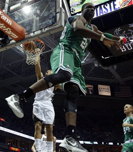 Milwaukee Bucks' Carlos Delfino, back left, dunks behind Boston Celtics' Mickael Pietrus (28) during the second half of an NBA basketball game on Thursday, March 22, 2012, in Milwaukee. (AP Photo/Jeffrey Phelps)