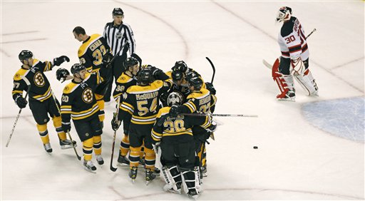 Boston Bruins center David Krejci is surrounded by teammates as New Jersey Devils goalie Martin Brodeur (30) skates off the ice after Krejci's game-winning goal during overtime of an NHL hockey game in Boston, Thursday, March 1, 2012. The Bruins won 4-3. (AP Photo/Charles Krupa)