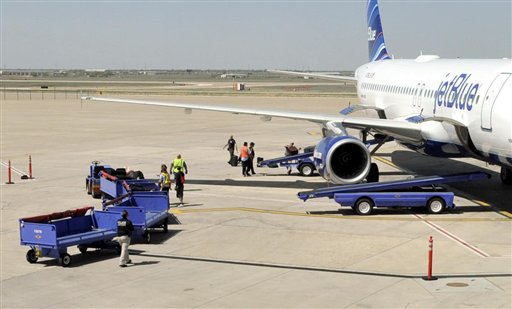 Officials remove baggage from JetBlue flight 191 and begin searching for explosives at Amarillo Rick Husband International Airport in Amarillo, Texas, Tuesday, March 27, 2012 after an unruly pilot caused the flight to make an emergency landing. (AP Photo/The Amarillo Globe News, Michael Schumacher)