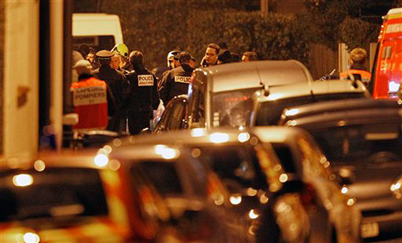 French police officers and firefighters stand at night next to the apartment building where a suspect in the shooting at the Ozar Hatorah Jewish school is still barricaded, in Toulouse, Southern France on Wednesday, March 21, 2012. A predawn police raid on a home in Toulouse erupted into a firefight Wednesday with a gunman who claims connections to al-Qaida and is suspected of killing three Jewish schoolchildren, a rabbi and three paratroopers. (AP Photo/Christophe Ena)