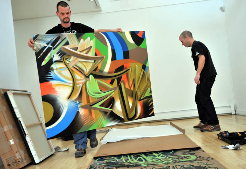 Portland graffiti artists Tim Clorius, left, and Matt W. Moore lay out pieces of their aerosol art exhibit Tuesday at the University of Maine at Farmington Art Gallery.