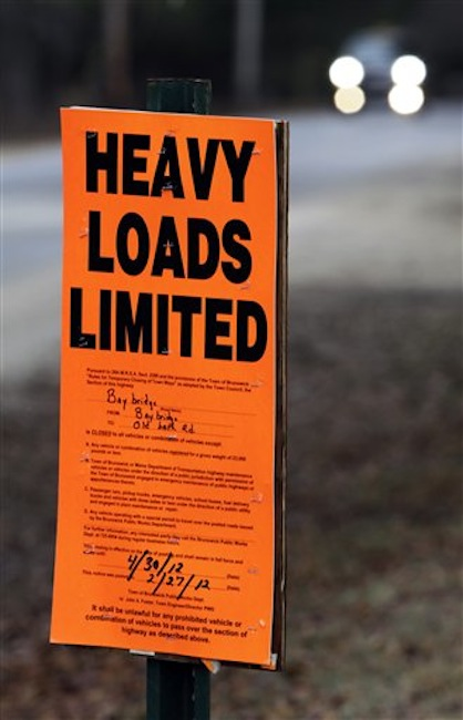 In this Wednesday, March 14, 2012 photo, a vehicle approaches a sign posted along a road prohibiting heavy trucks to use it in Brunswick, Maine. Hundreds of miles of roads are posted as the spring thaw comes early to northern New England. (AP Photo/Pat Wellenbach)