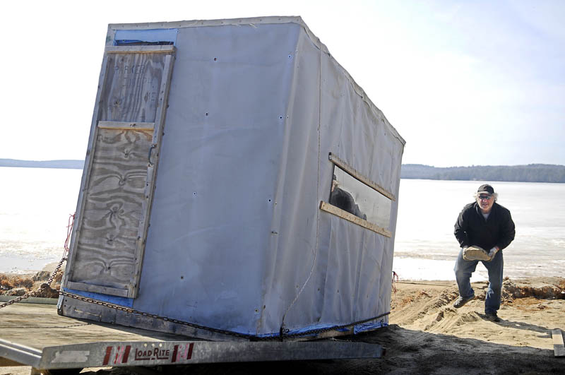 """Ron Poulin, of Waterville, collects a rock to block the tires on a trailer he utilized to load an ice fishing shack Monday on Damariscotta Lake in Jefferson. Poulin said he didn't have many opportunities to inhabit the shack this winter but still had a good season. """"We caught more smelts than we knew what to do with,"""" Poulin said."""