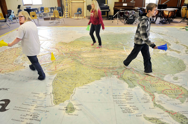 Maranacook Community High School freshman cross a giant map of Asia at the Readfield school.