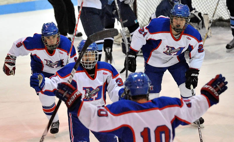 Messalonskee High School's Joshua Towle, 3, center facing, celebrates a first period goal against Presque Isle High School with teammates William Blake, 8, back left, Kalib Bernatchez, 21, back right, and Corey Foye, 10, foreground in the eastern regional play-off game at Sukee Arena in Winslow Saturday.