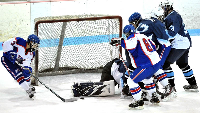 Messalonskee High School's Joshua Towle, 3, left, picks up the rebound for an early first period goal against Presque Isle High School in the eastern regional play-off game at Sukee Arena in Winslow Saturday.