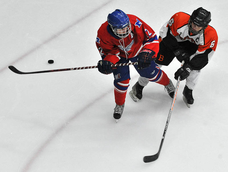 Photo by Michael G. Seamans Messalonskee High School's Chase Cunningham, 12, right, and Brewer High School's Jacob Chapman, 6, battle for the puck in the second period of the Class B East hockey regional finals at Alfond Arena at the University of Maine in Orono Tuesday night.