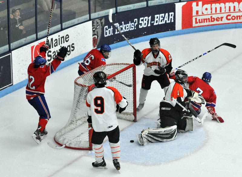 Photo by Michael G. Seamans Sam Dexter, 7, right, slides past the goalie after a goal in the second period of the Class B East hockey regional finals at Alfond Arena at the University of Maine in Orono Tuesday night.