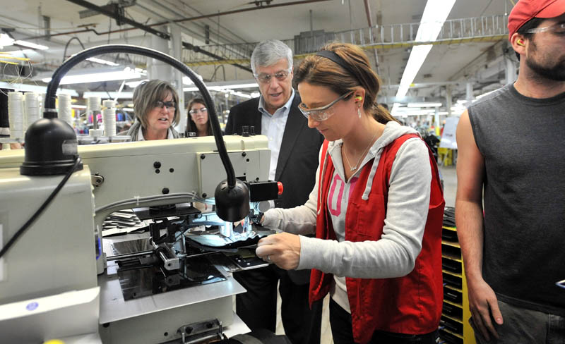 SPECIAL SHOES: Rep. Mike Michaud, center, speaks with New Balance factory employee Tiffany Whitney while touring the New Balance shoe factory in Norridgewock Friday morning. Michaud toured the plant and picked up a pair of size 12 D New Balance running shoes manufactured at the plant for President Obama.