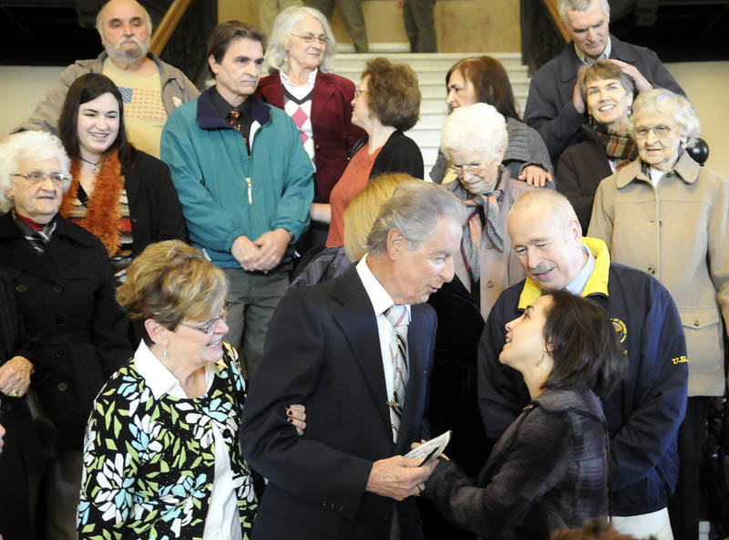 """Augusta resident Leo Pepin, center, is congratulated by relatives Monday after Gov. Paul LePage signed a bill designating a tune Pepin wrote, the """"Dirigo March,"""" as the state marching song at a State House ceremony in Augusta."""